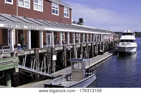 Halifax, Nova Scotia, September 23, 2015 -- Wide view of a large restaurant/store with a luxury boat and small fishing boat docked beside it on a bright sunny day in September in Halifax, Nova Scotia