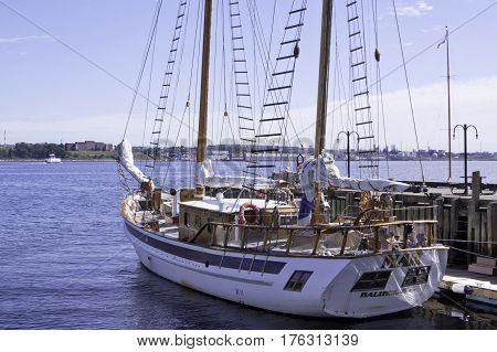 Halifax, Nova Scotia September 23 2015 -- Wide view of a wood trimmed sail boat docked at the Halifax Harbor on a beautiful bright sunny day in September with Dartmouth buildings in the background in Halifax, Nova Scotia
