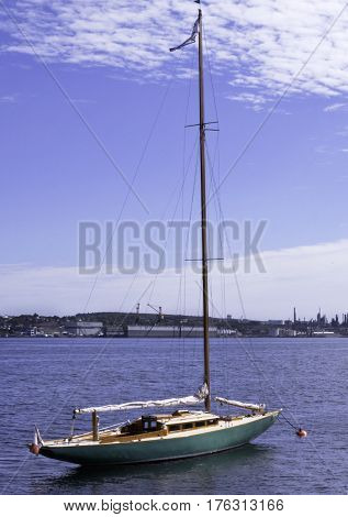 Halifax, Nova Scotia, September 23, 2015 -- Vertical view of a docked sailboat in the Halifax Harbor with the industrial buildings of Dartmouth in the background on a bright sunny day in Halifax, Nova Scotia