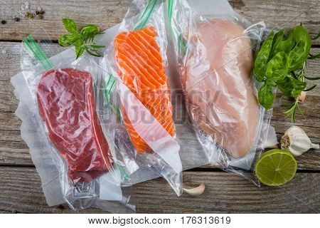 Beef, chicken and salmon in vacuum plastic bag for sous vide cooking, copy space