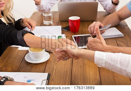 Business female handshake at office corporate meeting, contract conclusion and successful agreement concept. Closeup of businesswoman and other woman hands meet at wooden table background.