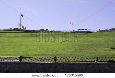 Halifax, Nova Scotia, September 23, 2015 -- Wide view of the lush green lawn leading up to citadel hill with flags blowing in the wind and people on the viewpoints on a bright sunny day in September