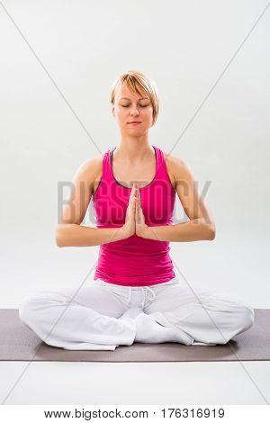 Photo of woman exercising yoga indoor-Lotus position/Padmasana