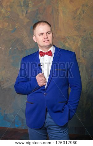 Happy elegant man in blue suit is standing at wall background.