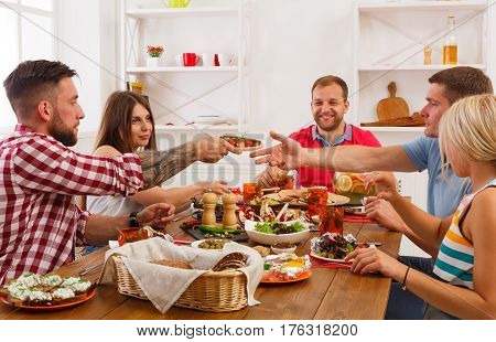 Group of people eat healthy meals at party dinner table in cafe, restaurant or at home. Young cute friends company celebrate with organic food at wooden table indoors.