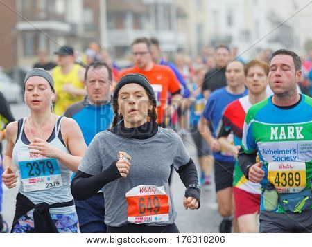 BRIGHTON GREAT BRITAIN - FEB 26 2017: Young girl and competitors running in the Vitality Brighton half marathon competition. February 26 2017 in Brighton Great Britain
