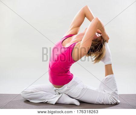 Woman exercising yoga indoor-One-legged king pigeon/Eka Pada Rajakapotasana