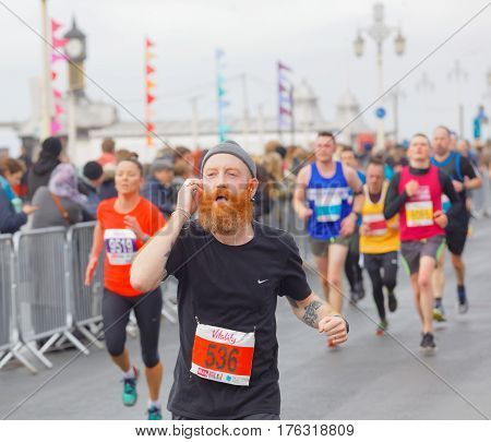 BRIGHTON GREAT BRITAIN - FEB 26 2017: Man with red beard and competitors running in the Vitality Brighton half marathon competition. February 26 2017 in Brighton Great Britain