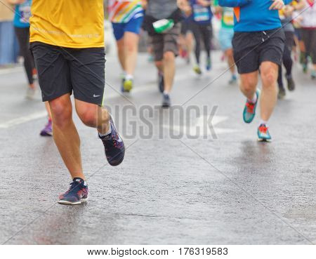 BRIGHTON GREAT BRITAIN - FEB 26 2017: Closeup of colorful male running feet and legs on wet asphalt in the Vitality Brighton half marathon competition. February 26 2017 in Brighton Great Britain