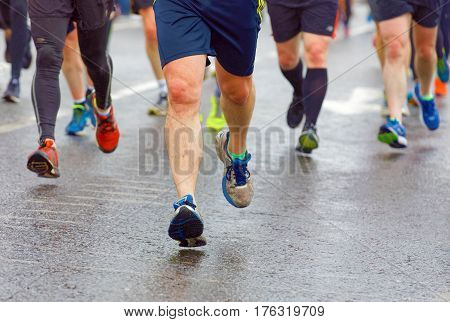 BRIGHTON GREAT BRITAIN - FEB 26 2017: Closeup of colorful running feet and legs on wet asphalt in the Vitality Brighton half marathon competition. February 26 2017 in Brighton Great Britain