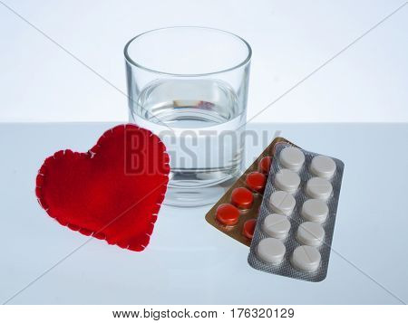 Heart glass of water and blister packs of pills