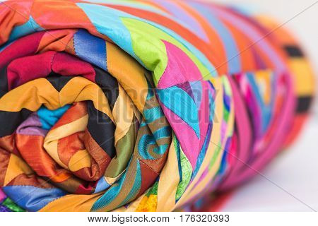Colored patchwork quilt twisted into close up. Colorful scrappy blanket folded as background. Handmade.