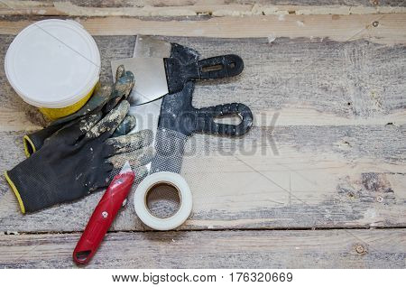 Renovation and construction concept, toolings on wooden floor background, working gloves, spatula, putty, knife and grid for cracks repair