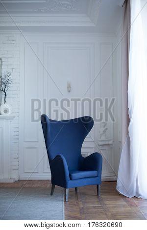 Empty blue cozy armchair in classical interior