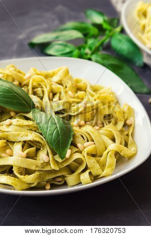 Fettuccine pasta with pesto sauce basil and pine nuts on concrete background. Italian cuisine. Selective focus.