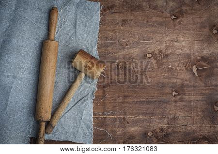Wooden kitchen items skalka and hammer for beating meat top view empty space