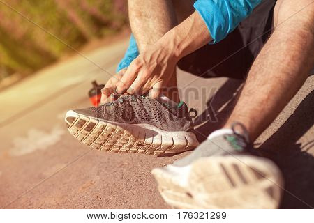 sportsman tie shoelaces on his running shoes in the park and bottle of water near