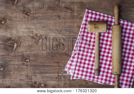 Wooden kitchen items on a red napkin rolling pin and hammer for beating meat top view empty space on the left