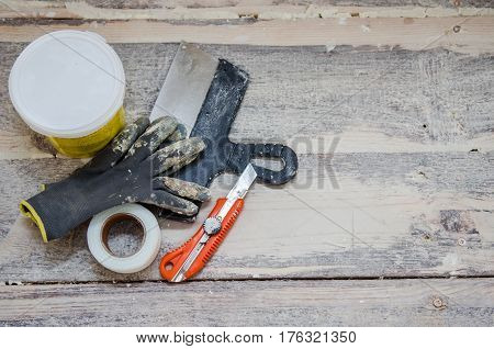 Renovation and construction concept, toolings on wooden floor background, working gloves, spatula and putty for cracks repair