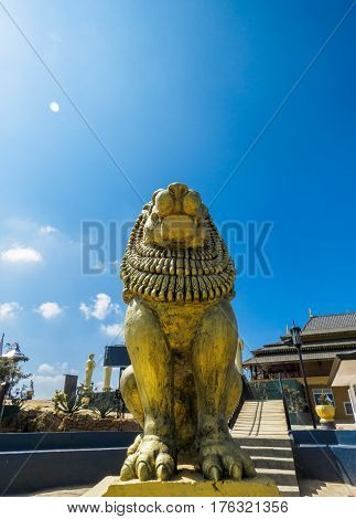 Brave Lion Posture sitting Statue on a mountain view top cliff with sun shine on top blue sky and clouds at Nelligala International Buddhist Center Kandy, Sri Lanka