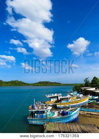 Beautiful Colorful Boats in Fishing Village by the Lagoon with Mangroves Blue sky and Clouds near Pulmoddai, Trincomalee, Sri Lanka
