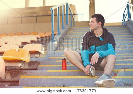 sportsman sitting with bottle of water on the stairs on the stadium