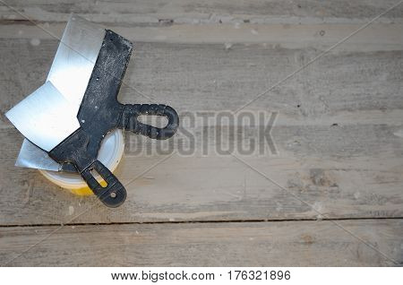 Renovation and construction concept, toolings on wooden floor background, spatula, putty for cracks repair