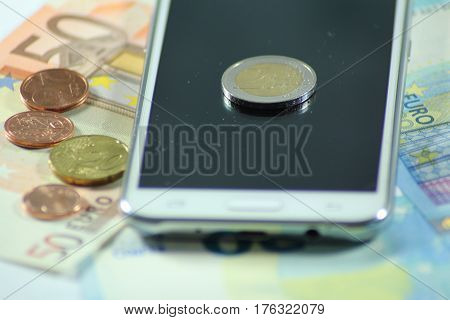 Euro banknote and coin with mobile phone/ These are twenty and fifty euro banknotes with phone.