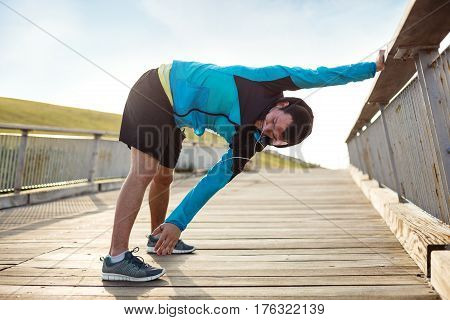 athletic sportsman doing warming stretching exercise in the park