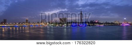 Panoramic view of Cairo city center at twilight the Kasr El Nile Bridge and the island of Zamalek with its colorful boats on the Nile river.