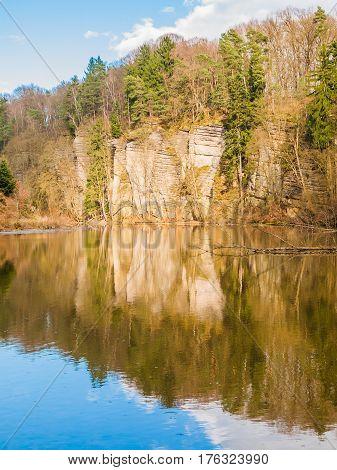 Sandstone rock formations reflected in the water. Plakanek Valley in Bohemian Paradise, aka Cesky Raj, Czech Republic, Europe.