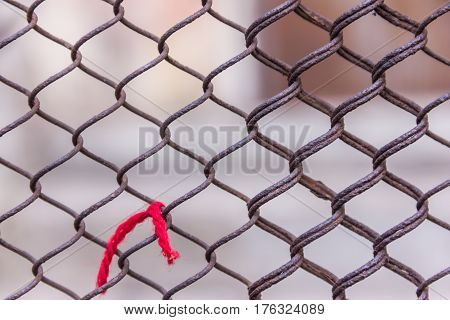 Rusty Steel Chain Link Or Wire Mesh As Boundary Wall. Red Thread. There Is Still Concrete Block Wall
