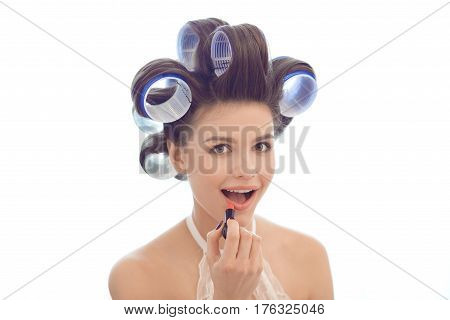 Woman in hair curlers applying make-up at home against white background. Brunette girl in sexy lingerie on white background. Model preparing to party carefully applies lipstick while looking at camera like in a mirror indoors at home against bright window
