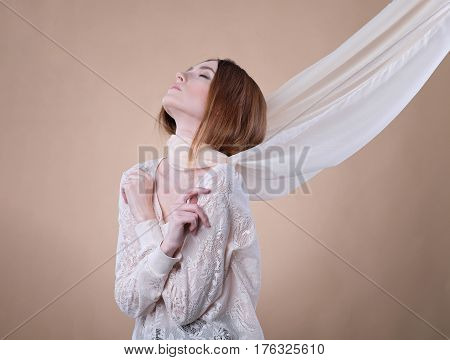 Girl in shawl posing in studio on beige background. She dressed on translucent blouse. The light scarf on her neck twists in the wind. Her arms crossed near chest, eyes lowered, head up.