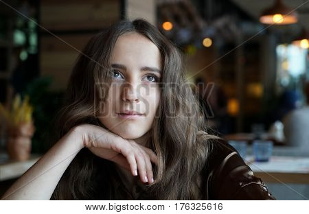 Close-up portrait of young dreaming girl in cafe. Beautiful girl sits in coffee shop and looks, lost in thought, hand near face, eyes up. Сurly hair, big brown eyes, natural make-up
