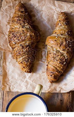 Whole wheat croissants with seeds on piece of craft paper enamel mug with milk breakfast top view cozy atmosphere
