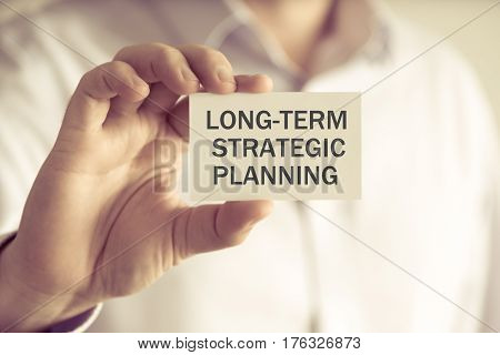 Businessman Holding Long-term Strategic Planning Message Card