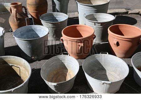 many aluminum buckets and clay pots for sale at the market