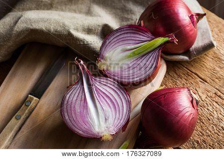 Red or purple onion cut in half wood breadboard linen towel knife kitchen table by window rustic style
