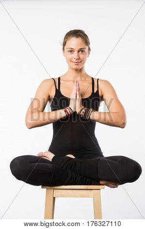 beautiful woman sit on a chair in meditative pose isolated on white.