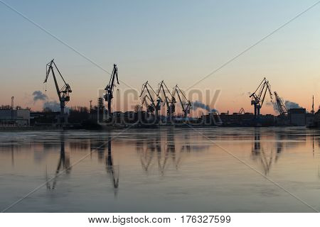 Silhouettes portal cranes reflection on water port St. Petersburg