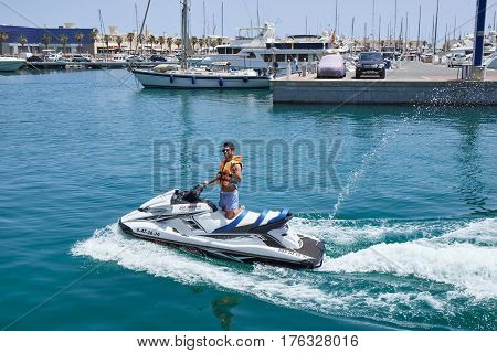 Alicante, Spain - June 30, 2016: A young male riding jet ski at lake on sunny day
