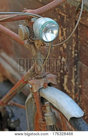 Old rusty bicycle with still functioning headlight
