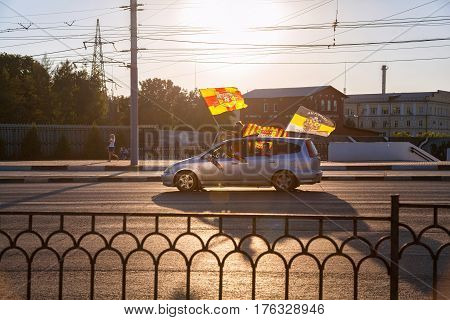 Tula, Russia - August 6, 2016: Fans of football club Tula Arsenal celebrate their victory by riding a car through the city with flags of the club