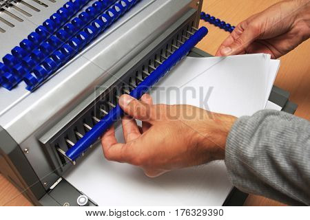 Gray Binding machine with man who works on it
