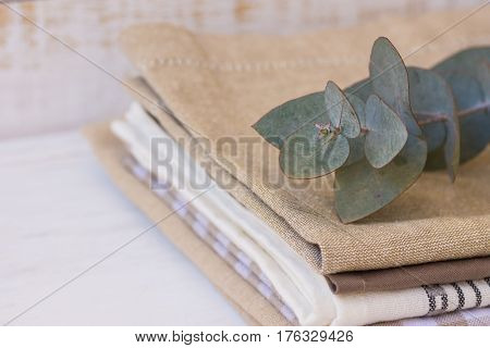 Pile of stacked linen and cotton kitchen towels with branch of silver dollar eucalyptus on white wood table interior design concept template closeup