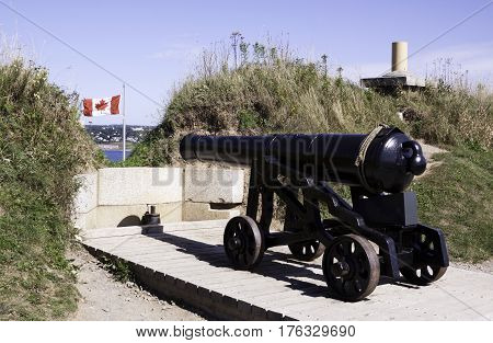 Halifax, Nova Scotia, September 23, 2015 -- Close up of a large iron canon pointing out towards the Halifax Harbor with a Canadian flag blowing brightly in the background on a bright sunny day in September