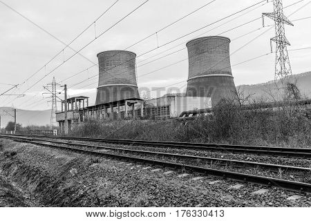 Black and white Cooling towers of thermal power plant near the railway