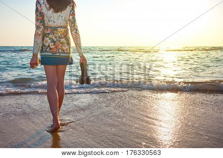 young and beautiful woman in colorful dress standing on the beach near the ocean and looking far away at the sunset