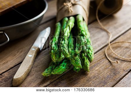 Bunch of fresh asparagus tied with twine garlic knife kitchenware on wood table cooking concept closeup